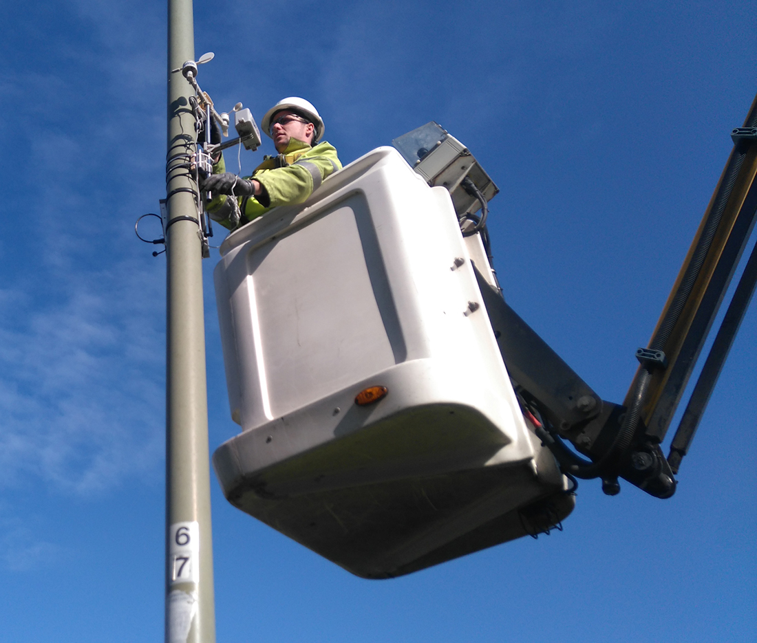 A technician installing the Weather Station